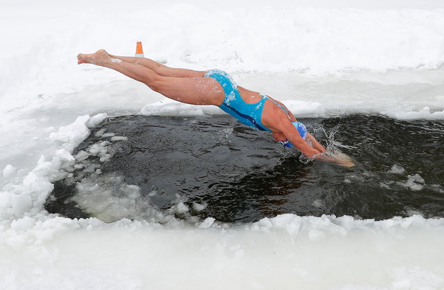 """Natalya Seraya, chairwoman of """"Walruses of the Capital"""" winter swimming club, dives into the icy waters of the Moskva River on a frosty day in Moscow, Russia on February 13, 2021. (Photo by Evgenia Novozhenina/Reuters)"""