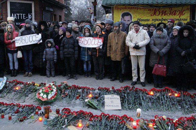 "People hold placards with the slogan ""I am Bosse"" during a mourning ceremony for victims killed in the shelling of a bus stop, in Donetsk, eastern Ukraine, January 24, 2015. (Photo by Alexander Ermochenko/Reuters)"