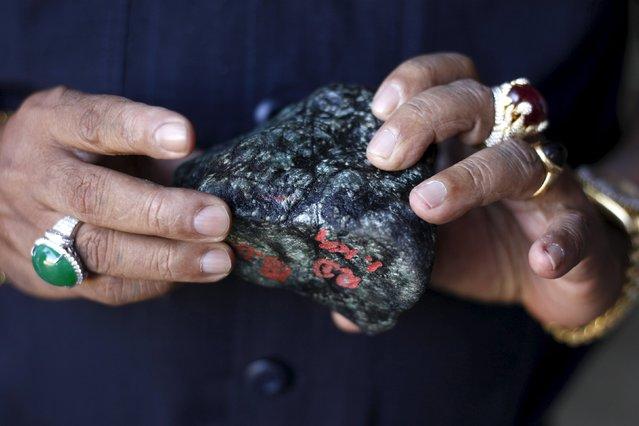 A buyer checks a jade stone near a mine dump at a Hpakant jade mine in Kachin state, Myanmar November 29, 2015. (Photo by Soe Zeya Tun/Reuters)