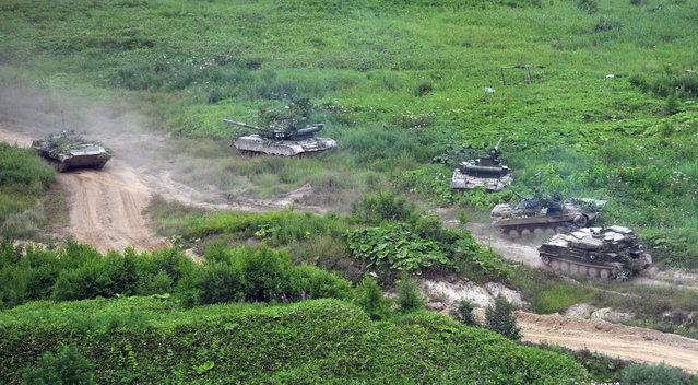 Russian Army tanks move at the Sakhalin Island during military exercises on Tuesday, July 16, 2013. (Photo by Alexei Nikolsky/AP Photo/RIA Novosti/Presidential Press Service)