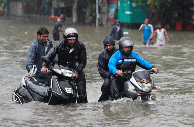 A man pushes his scooter as another rides his motorcycle through a waterlogged street during heavy rains in Mumbai, July 9, 2018. (Photo by Danish Siddiqui/Reuters)