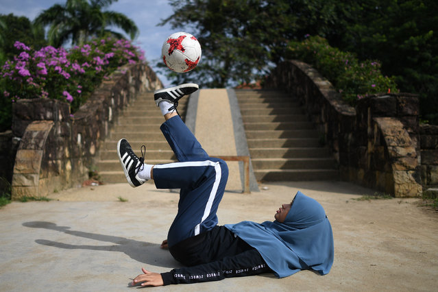 In this photograph taken on July 11, 2018, female football freestyler Qhouirunnisa' Endang Wahyudi, 18, juggles the ball at a park in Klang, on the outskirts of Kuala Lumpur Sporting a headscarf, Qhouirunnisa' Endang Wahyudi executed deft moves, juggling the ball before balancing it on her soles and later on her forehead. The slick freestyle football moves of a Malaysian Muslim girl have boosted her into the spotlight in a country where the sport is dominated by men. (Photo by Mohd Rasfan/AFP Photo)