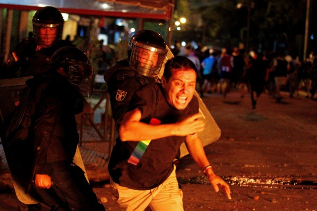 Riot police officers clash with a demonstrator during a protest against President Mario Abdo Benitez's health policies and the lack of coronavirus disease (COVID-19) vaccines in Asuncion, Paraguay on March 5, 2021. (Photo by Cesar Olmedo/Reuters)