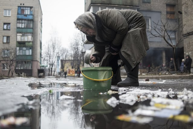 An elderly woman collects water from a puddle in Debaltseve, February 3, 2015. (Photo by Sergey Polezhaka/Reuters)
