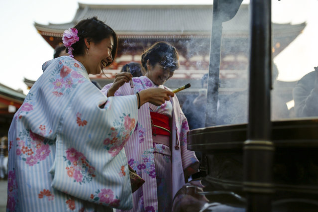 Women in kimonos burn incense sticks at the Sensoji temple ahead of the New Year holidays in Tokyo, Japan December 30, 2015. (Photo by Thomas Peter/Reuters)