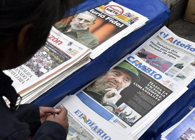 A girl looks at newspapers' front pages at a kiosk in La Paz on November 26, 2016, the morning after Cuba's historic revolutionary leader Fidel Castro died aged 90. One of the world's longest-serving rulers and modern history's most singular characters, Castro defied 11 US administrations and hundreds of assassination attempts. (Photo by Aizar Raldes/AFP Photo)
