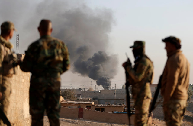 Iraqi soldiers look as smoke rises over the village of Al-Qasar during fighting between Iraqi soldiers and Islamic State fighters South-East of Mosul, Iraq November 28, 2016. (Photo by Goran Tomasevic/Reuters)