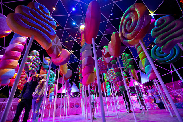 "Guests pose for photos by an installation at the ""Sugar Rush"" experience, a candy-based theme park, in Woodland Hills, California, U.S., April 1, 2021. (Photo by Mario Anzuoni/Reuters)"