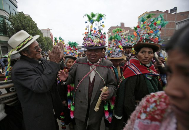 A man applauds to members of the San Pedro de Cota group during the Anata Andina (Andean carnival) in Oruro February 12, 2015. (Photo by David Mercado/Reuters)