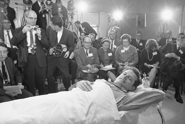 Sen. Edward M. Kennedy smiles happily as he held a press conference at New England Baptist Hospital in Boston October 19, 1964. Sen. Kennedy described the plane crash in which his back was broken four months ago today while strapped in the orthopedic frame to which he has been confined since the accident. The pilot of the plane and a Kennedy aide were killed in the June 19 accident in Western Massachusetts. (Photo by AP Photo)