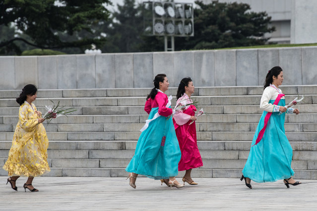 North Korean women in traditional dress run to catch up as they pay their respects to the Mansudae Grand Monument, huge statues of Kim Il-sung and Kim Jong-il, on August 19, 2018 in Pyongyang, North Korea. (Photo by Carl Court/Getty Images)