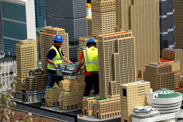 "Workers carry the skating rink portion of Rockefeller Center as they work on the New York City section of the ""Miniland"" area of the new Legoland New York Resort theme park during a press preview of the park, which is currently under construction, with plans to open to the public in the summer of 2021 in Goshen, New York, U.S., April 28, 2021. (Photo by Mike Segar/Reuters)"