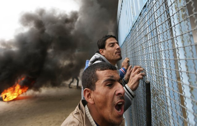 Smoke rises from burning tyres as Palestinians shout during a protest calling for reconstruction of their houses that witnesses said were destroyed by Israeli shelling during a 50-day war last summer, outside a United Nations food distribution center in Rafah in the southern Gaza Strip February 16, 2015. (Photo by Ibraheem Abu Mustafa/Reuters)
