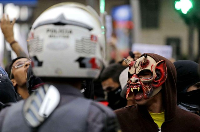 A demonstrator wears a mask during a protest against the fare hike on public transportation in Sao Paulo, Brazil, Tuesday, January 12, 2016. The protests were organized by the Free Fare Movement, the same group that initiated mass anti-government demonstrations that filled streets across Brazil in 2013. (Photo by Nelson Antoine/AP Photo)