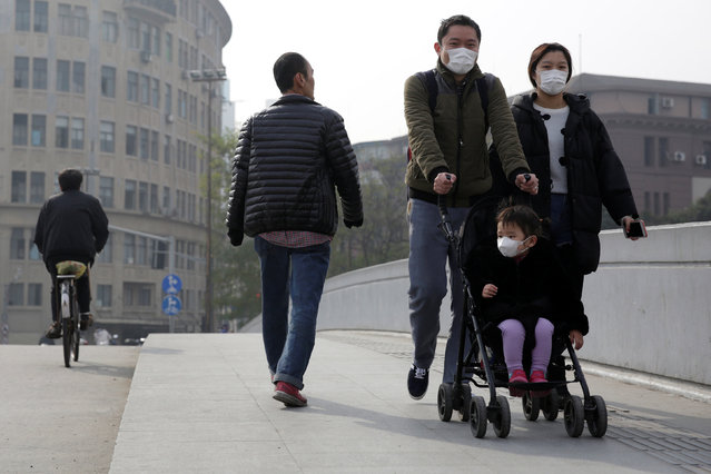 A family wearing masks walk on a bridge amid heavy smog in Shanghai, China December 5, 2016. (Photo by Aly Song/Reuters)