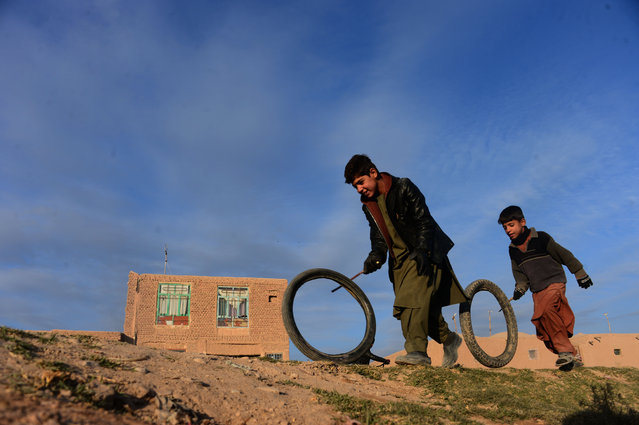 Afghan boys play with tyres along a street on the outskirts of Herat on November 24, 2016. (Photo by Aref Karimi/AFP Photo)