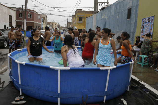 A group of women dance in a pool in Callao, Peru, Sunday, February 22, 2015. One of centers for the front-doorstep, pool-party phenomenon is Lima's port city of Callao. People hold parties in them and sometimes entire blocks chip in to buy a pool, which can be had in local department stores for a bit over $100. (Photo by Martin Mejia/AP Photo)