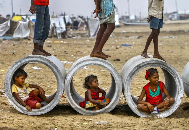 Children sitting inside cement water pipes play on the Marina beach in the southern Indian city of Chennai, on Oktober 10, 2013. (Photo by Reuters/Babu)