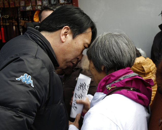 A plain clothed policeman (L) talks to a family member of passengers onboard the missing Malaysia Airlines flight MH370, as he stops the family member holding a paper bearing a slogan outside Yonghegong Lama Temple after a gathering of family members of the missing passengers in Beijing March 8, 2015. Prime Minister Najib Razak said on Sunday Malaysia remains committed to the search for the missing MH370 jetliner a year after it vanished without trace and he is hopeful it will be found.