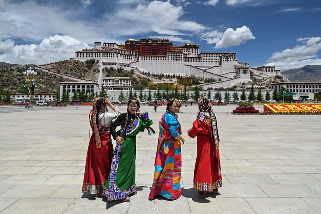 This photograph taken during a government organised media tour shows people in traditional costume standing in Potala Palace Square as the Potala Palace – classified as a World Heritage Site by Unesco in 1994 – is seen in the background in the regional capital Lhasa, in China's Tibet Autonomous Region, on June 1, 2021. (Photo by Hector Retamal/AFP Photo)