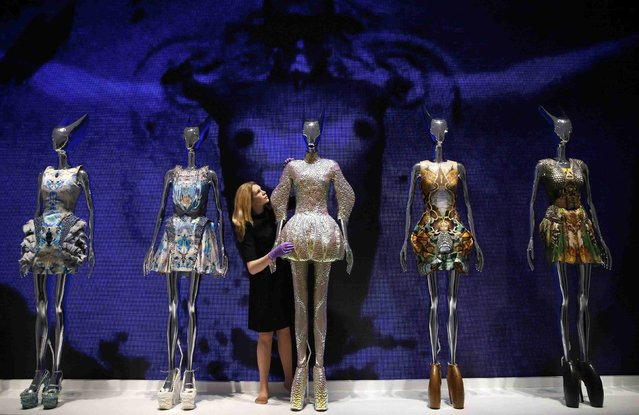 A staff member poses with dresses from the Alexander McQueen Plato's Atlantis spring/summer 2010 collection  in the Alexander McQueen: Savage Beauty exhibition at the V&A in London, March 12, 2015. (Photo by Suzanne Plunkett/Reuters)
