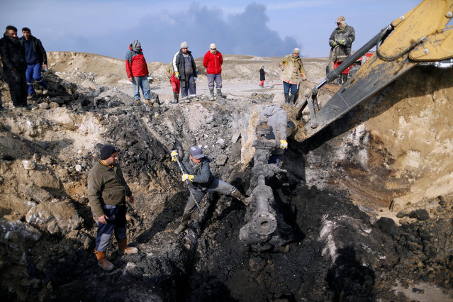 Oil workers react in front of oilfields burned by Islamic State fighters in Qayyara, south of Mosul, Iraq December,21, 2016. (Photo by Ammar Awad/Reuters)
