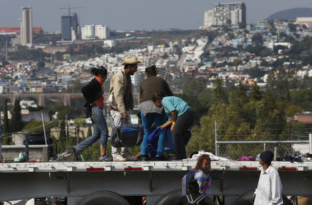 Central American migrants arrive in Queretaro, Mexico, as they resume their journey north after leaving the temporary shelter in Mexico City, Saturday, November 10, 2018. Thousands of Central American migrants were back on the move toward the U.S. border Saturday, after dedicated Mexico City metro trains whisked them to the outskirts of the capital and drivers began offering rides north. (Photo by Marco Ugarte/AP Photo)