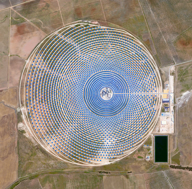 "Solar Concentrator 37°33'38.0""N, 5°19'53.1""W. The Gemasolar Solar Concentrator in Seville, Spain, contains 2,650 heliostat mirrors that focus the sun's thermal energy to heat molten salt flowing through a 460-ft-tall (140m) central tower. The molten salt then circulates from the tower to a storage tank, where it is used to produce steam and generate electricity. In total, the facility displaces approximately 30,000 tonnes of carbon dioxide emissions every year. (Photo by Daily Overview/DigitalGlobe, a Maxar Company)"