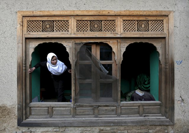 An Afghan girl looks out of a damaged window of a shrine after a suicide attack in Kabul March 25, 2015. (Photo by Omar Sobhani/Reuters)