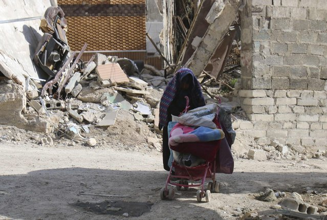 A woman collects objects from damaged buildings in Jobar, a suburb of Damascus, January 5, 2015. (Photo by Diaa Al-Din/Reuters)