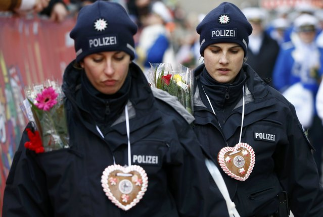 """German police officers walk during the """"Rosenmontag"""" (Rose Monday) parade, the highlight of the annual carnival season in Cologne, Germany February 8, 2016. Cologne city authorities decided to go ahead with Monday's parade, despite many other traditional Rose Monday carnival parades being cancelled in the Rhineland due to severe weather warnings. (Photo by Wolfgang Rattay/Reuters)"""