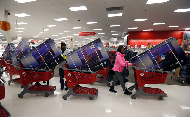 Thanksgiving Day holiday shoppers line up with television sets on discount at the Target retail store in Chicago, Illinois, November 28, 2013. About 140 million people are expected to shop over the four-day weekend, according to the National Retail Federation. (Photo by Jeff Haynes/Reuters)