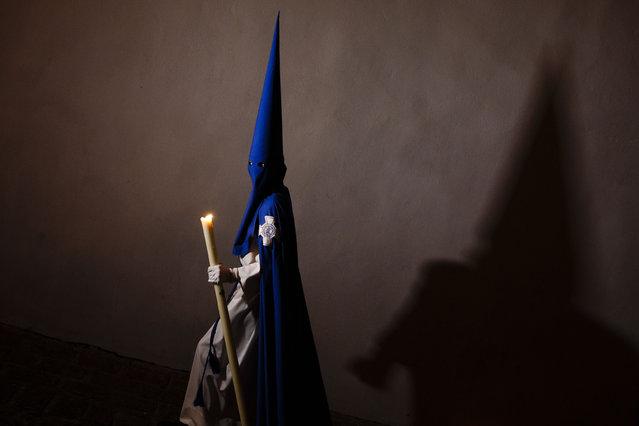 """A penitent casts his shadow as he takes part in """"Nuestro Senor Atado a la Columna, Maria Santisima de la Paz y San Juan Evangelista"""" Holy Week procession in Arcos de la Frontera, Spain, Tuesday, March 31, 2015. (Photo by Daniel Ochoa de Olza/AP Photo)"""