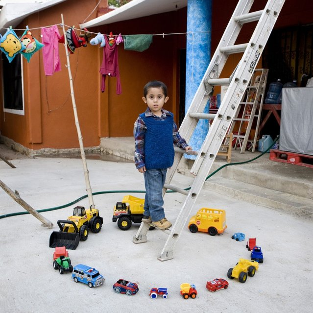 "Abel – Nopaltepec, Mexico. Abel, the third of five children, was born and raised in the small town of Nopaltepec, about an hour southeast of Mexico City. In this photo he's posing with all of his games. He loves to race with his toy cars, and sometimes plays with them with his younger sister. ""Toy Stories"" project. (Gabriele Galimberti)"