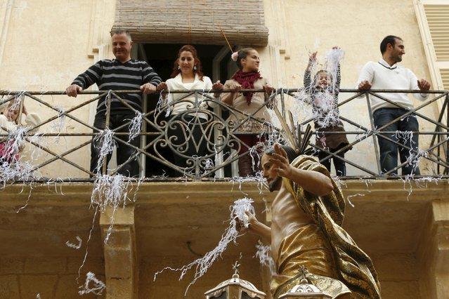 People in a balcony throw confetti over a statue of the Risen Christ during an Easter Sunday procession in Cospicua, outside Valletta April 5, 2015. (Photo by Darrin Zammit Lupi/Reuters)
