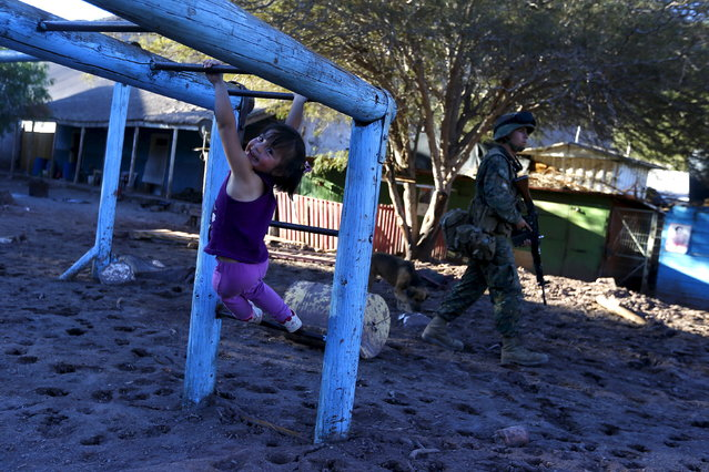 A child plays in a playground covered with dried mud at San Antonio town, April 7, 2015. (Photo by Ivan Alvarado/Reuters)