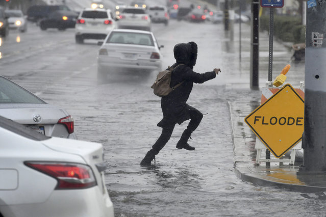 A pedestrian leaps across a flooded portion of the La Paz and Seventh Street intersection as a winter storm arrived, Thursday, December 6, 2018 in Victorville, Calif. The second round of a fall storm dumped snow and rain that jammed traffic on Southern California highways and loosened hillsides in wildfire burn areas on Thursday. (Photo by James Quigg/The Daily Press via AP Photo)