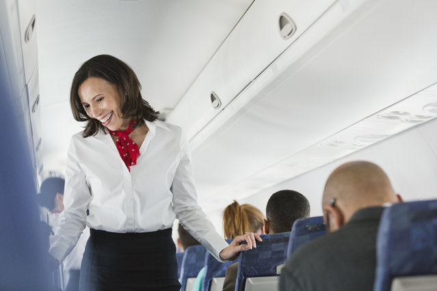Flight attendant talking to passengers in airplane. (Photo by Getty Images/Hero Images)