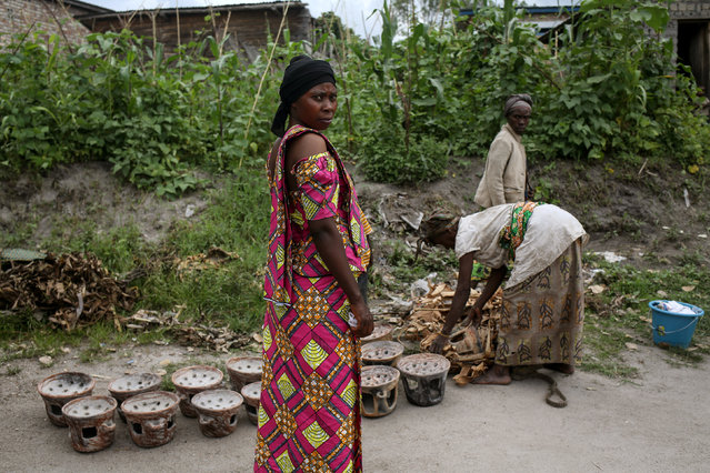 A Bahavu woman stands (L) as Pygmy women sell pottery in the Bahavu village of Bugarula on Idjwi island in the Democratic Republic of Congo, November 23, 2016. (Photo by Therese Di Campo/Reuters)