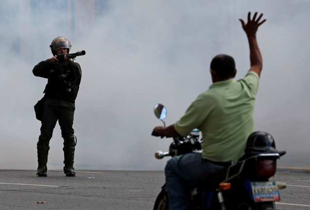 A man on a scooter lifts his hand opposite a security forces officer during a protest of opposition supporters against Venezuelan President Nicolas Maduro's government in Caracas, Venezuela, January 23, 2019. (Photo by Carlos Garcia Rawlins/Reuters)