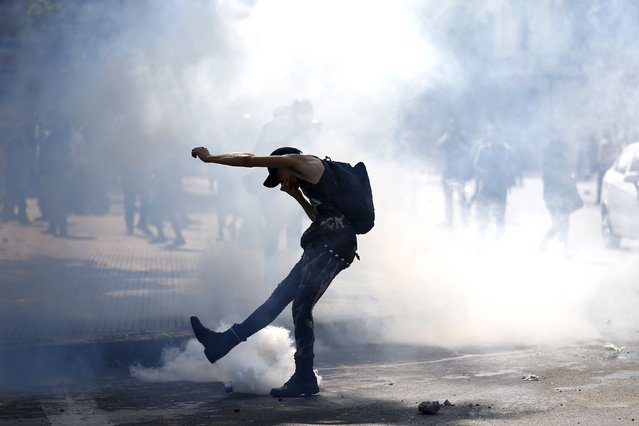 A protester kicks a tear gas canister as they clash with riot police during a demonstration against the government to demand changes in the education system at Santiago, April 16, 2015. (Photo by Ivan Alvarado/Reuters)