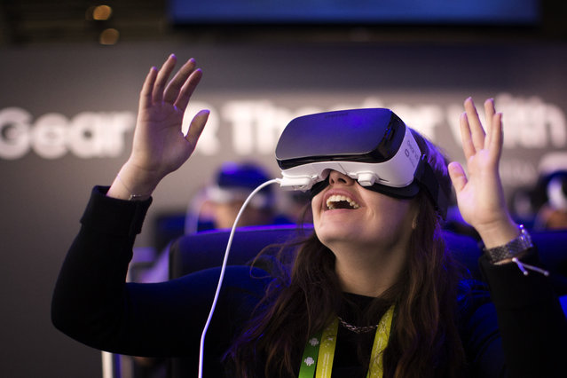 A woman reacts as she uses a new Samsung Gear 360, a 360-degree camera, at the Mobile World Congress wireless show, in Barcelona, Spain, Monday, February 22, 2016. (Photo by Emilio Morenatti/AP Photo)