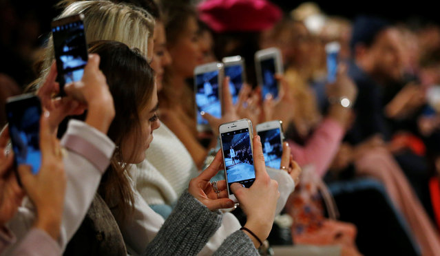 A so-called media influencer takes pictures as a model presents a creation by Marina Hoermanseder on the sidelines of the Berlin Fashion Week Autumn/Winter 2017/2018 in Berlin, Germany January 19, 2017. (Photo by Hannibal Hanschke/Reuters)