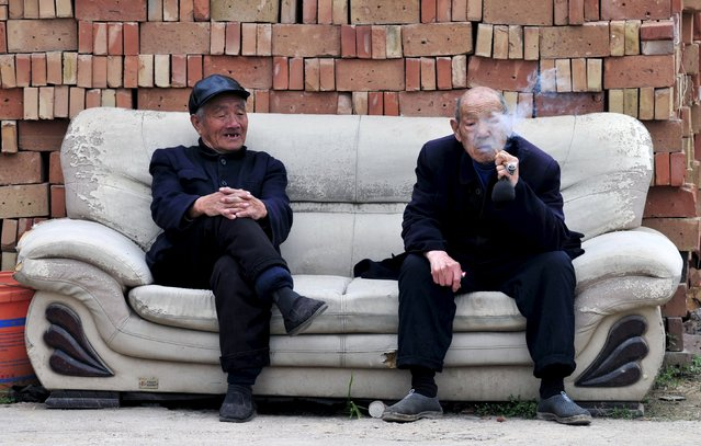 An elderly man (R) smokes a pipe as he chats with another man on a sofa in front of piles of bricks in Yongji, Shanxi province April 11, 2015. China's state pension funds will likely have a funding gap in future due to growing obligations, Vice Finance Minister Wang Baoan said on April 3. (Photo by Reuters/Stringer)
