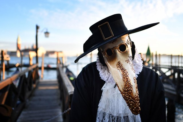 A reveller wearing a mask and a period costume smells a rose as he takes part in the Venice Carnival on February 24, 2019 in Venice. (Photo by Alberto Pizzoli/AFP Photo)