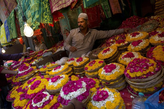 Indian muslims sell petals and garlands to devotees for offering at the shrine of Sufi saint Khwaja Moinuddin Chishti during the Urs festival in Ajmer, in the western Indian state of Rajasthan, India, Friday, April 24, 2015. Thousands of pilgrims from different parts of India have arrived in the city for the yearly Urs that marks the death anniversary of the sufi saint. (Photo by Bernat Armangue/AP Photo)