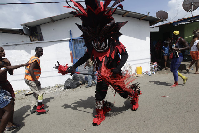 """A man dressed in a devil costume approaches pedestrians during the """"Diablos y Congos"""", an Ash Wednesday ritual that marks the end of Carnival and the start of the Lenten season in Nombre de Dios, Panama, Wednesday, March 6, 2019. The ritual involves dancers in devil costumes who go about scaring the """"sinners"""" who have been partying for days during carnival. (Photo by Arnulfo Franco/AP Photo)"""