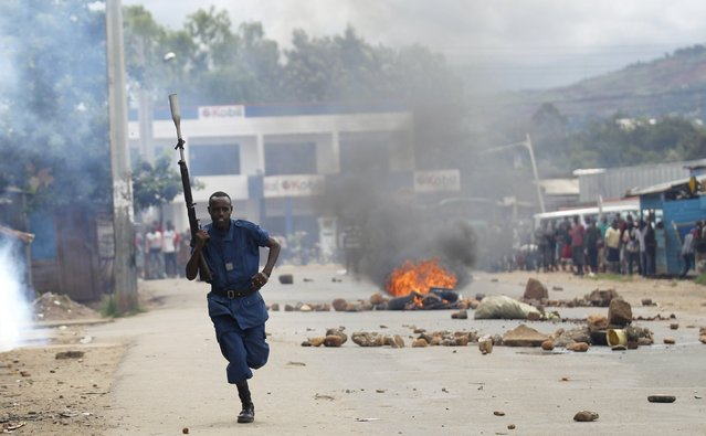 A riot policeman runs past a bonfire during street protests against the decision made by Burundi's ruling National Council for the Defence of Democracy-Forces for the Defence of Democracy (CNDD-FDD) party to allow President Pierre Nkurunziza to run for a third five-year term in office, in the capital Bujumbura, April 26, 2015. (Photo by Thomas Mukoya/Reuters)