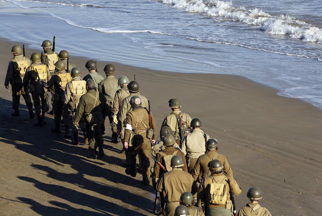 Volunteers wearing the uniform of the U.S. army participate in the re-enactment of a World War Two landing to mark its 70th anniversary in Anzio, near Rome, January 25, 2014. (Photo by Stefano Rellandini/Reuters)