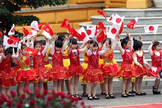 Children wave flags during a welcome ceremony of Japanese Prime Minister Shinzo Abe (not pictured) at the Presidential Palace in Hanoi, Vietnam January 16, 2017. (Photo by Luong Thai Linh/Reuters)